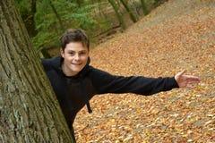 十几岁的男孩在秋天森林里 免版税库存图片
