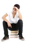 十几岁的男孩坐书等待 免版税库存图片