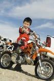 十几岁的男孩坐他的马达自行车 库存照片