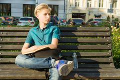 十几岁的男孩室外画象13, 14岁坐长凳在城市公园 免版税图库摄影