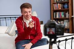 十几岁的男孩录音录影他自己在卧室 库存照片
