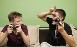 十几岁的男孩戏弄的弟弟,当打电子游戏时 免版税库存图片