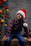 十几岁的男孩画象在圣诞老人` s帽子和格子花呢上衣穿戴了 免版税库存图片