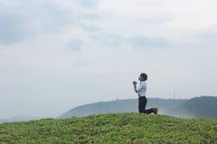 十几岁的男孩祈祷 免版税库存照片