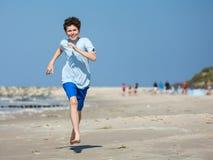 十几岁的男孩赛跑,跳跃在海滩 库存图片