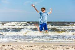 十几岁的男孩跳跃,跑在海滩 免版税库存照片