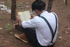 十几岁的男孩阅读书在森林 免版税库存照片