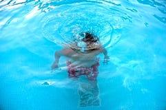 年轻十几岁的男孩水下在游泳池 库存照片