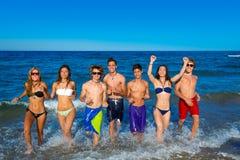 十几岁编组连续愉快飞溅在海滩 免版税图库摄影
