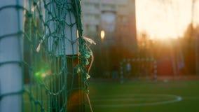 十几岁踢横跨橄榄球目标的足球夏天晚上,非被聚焦的背景 库存照片
