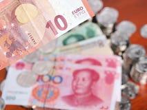 十在堆的欧元笔记硬币和中国人元笔记前面 免版税库存照片