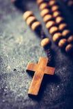 十字架和念珠在石背景 免版税库存照片