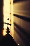十字架在有太阳射线的教会里 免版税库存图片