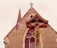 十字架的耶稣与背景阴霾的维多利亚女王时代的教会 库存照片