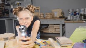 十岁的女孩画象在拿着一个电子钻子的木木匠业方面,摆在照相机 一点建造者概念 HD 股票视频