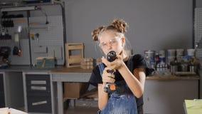 十岁的女孩画象在拿着一个电子钻子的木木匠业方面,摆在照相机 一点建造者概念 HD 影视素材