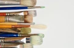 十把不同被塑造的艺术家` s油漆刷水平地在白色地面安排了 免版税图库摄影