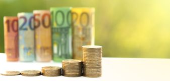 十,二十,五十,一百,二百和硬币欧元在绿色被弄脏的bokeh背景滚动了票据钞票 直方图fr 免版税库存照片