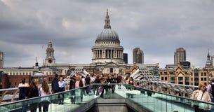 千年桥梁。 背景是圣保罗的大教堂在伦敦 库存照片