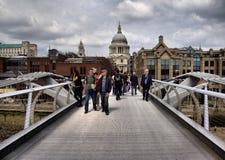 千年桥梁。 背景是圣保罗的大教堂在伦敦 图库摄影