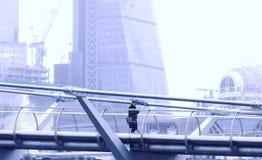 千年桥梁,伦敦英国 2018年1月20日 有发短信的伞的一个夫人,她沿千年桥梁在雨中单独走 免版税库存图片