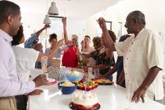 千福年的非裔美国人的妇女倾吐的香槟在三一代家庭庆祝时在家 免版税库存照片
