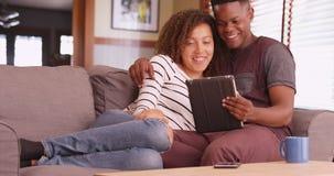 千福年的夫妇坐在他们的片剂计算机上的长沙发观看的电影 免版税库存照片