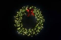 升在藏青色墙壁上的圣诞节花圈 免版税库存照片