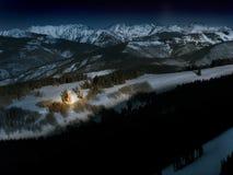 升山圣诞树在雪明亮地发光在晚上 库存图片