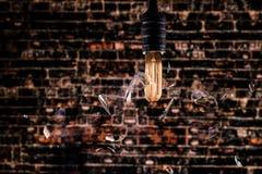 升打碎在细丝之前的爱迪生电灯泡烧光 免版税库存照片