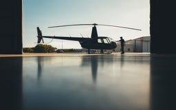 直升机剪影在有飞行员的飞机棚 免版税图库摄影