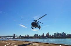 直升机和布鲁克林大桥和曼哈顿桥梁在东部Ri 免版税库存照片