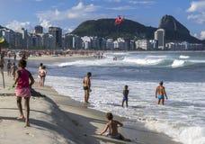 直升机在里约热内卢,巴西降低在科帕卡巴纳海滩上的一位被抢救的游泳者 免版税库存照片