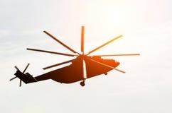 直升机的巨大的剪影在从太阳的天空强光飞行  图库摄影