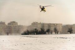 直升机飞行与在绳索的装载在多雪的领域 免版税库存图片