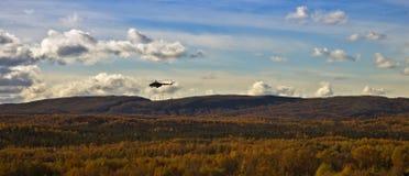 直升机飞行在秋天小山 免版税图库摄影