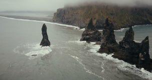 直升机飞行远离在海的黑火山的海滩和拖钓脚趾峭壁在冰岛 在雾的美好的风景 股票录像