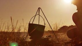 升营火在露营地远足者水的远足者止步不前在常礼帽大锅努力去做烟阳光在日落的水壶煮沸 影视素材