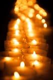 升蜡烛连续 烧在晚上的圣诞节蜡烛在教会里 免版税库存照片