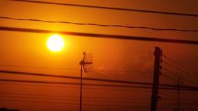 升起在导线之间的太阳 免版税库存图片