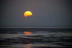 升起在海洋的太阳,部分地被盖 免版税图库摄影