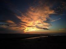 升起在海滩的太阳 免版税库存图片