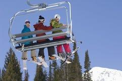 升降椅的三个滑雪者 库存照片