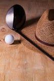 午睡-草帽和高尔夫球司机在一张木书桌上 库存照片