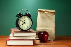 午餐、苹果计算机、书和时钟在书桌上在学校 免版税库存照片