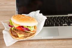 午餐在膝上型计算机附近的工作地点 库存照片