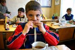 午餐时间在一所农村学校,男小学生吃午餐 库存照片