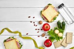 午餐盒用三明治和新鲜蔬菜、瓶水,坚果和鸡蛋在白色木背景 顶视图 免版税库存图片