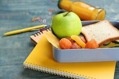 午餐盒用另外食物和文具在桌上 库存照片