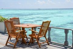 午餐设定了与木桌和椅子在餐馆在海洋附近 免版税库存图片
